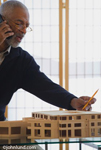 Architect talking on cell phone and pointing to a model of a building on his desk. The man is older with gray hair and a gray beard.  He is a black architect.